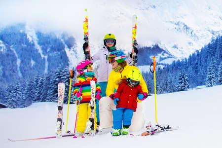 narciarz: Matki i dzieci jazdy na nartach w górach. Aktywna mama i troje dzieci z kask, gogle i tyczkach. nauka jazdy na nartach dla małych dzieci. Sport Zima i śnieg zabawa dla rodziny. Dziecko uczy się jeździć na nartach