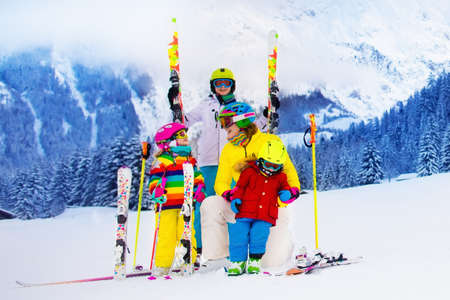 skis: Mother and children skiing in the mountains. Active mom and three kids with safety helmet, goggles and poles. Ski lesson for young children. Winter sport and snow fun for family. Child learning to ski