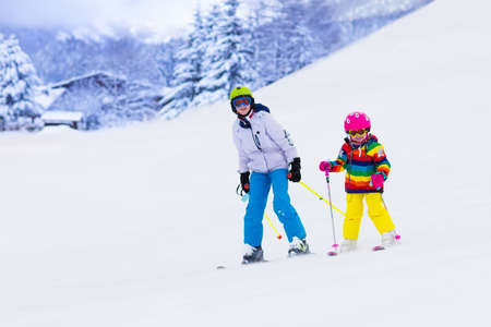 to ski: Boy and girl skiing in mountains. Toddler kid and teenager with helmet, goggles, poles. Ski race for children. Winter sport for family. Kids ski lesson in alpine school. Little skier racing in snow
