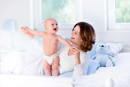 Mother and child on a white bed. Mom and baby boy in diaper playing in sunny bedroom. Parent and little kid relaxing at home. Family having fun together. Bedding and textile for infant nursery.