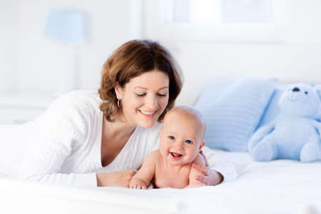 mother baby: Mother and child on a white bed. Mom and baby boy in diaper playing in sunny bedroom. Parent and little kid relaxing at home. Family having fun together. Bedding and textile for infant nursery.