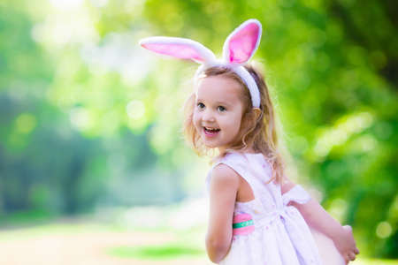 Little girl having fun on Easter egg hunt. Kids in bunny ears and rabbit costume. Children searching for eggs in the garden. Toddler kid playing outdoor. Child laughing and smiling on a spring day