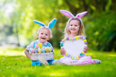 Little boy and girl having fun on Easter egg hunt. Kids in bunny ears and rabbit costume. Children with colorful eggs in a basket. Toddler kid and baby play outdoor. Blank board for your text.