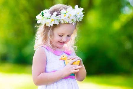 Petite fille amusant sur la chasse aux ?ufs de Pâques. Kid couronne de fleurs en jouant avec le canard de jouet ou de poulet. Les enfants à la recherche d'oeufs dans le jardin. Toddler Outdoor Enfants. enfant heureux rire et sourire. Banque d'images