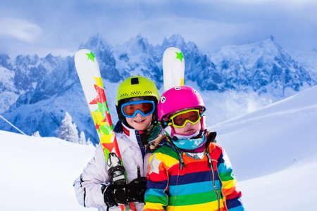 Jongen en meisje skiën in de bergen. Peuter kind en tiener met helm, bril, polen. Ski-race voor kinderen. Wintersport voor familie. Kids ski les in alpine school. Weinig skiër racen in de sneeuw Stockfoto - 50959764