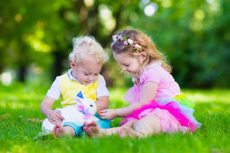 girl care: Children play with real rabbit. Brother and sister at Easter egg hunt with white pet bunny. Little baby boy and toddler girl playing with animal in the garden. Summer outdoor fun for kids with pets. Stock Photo