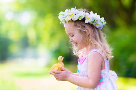 Little girl having fun on Easter egg hunt. Kid in flower crown playing with toy duck or chicken. Children searching for eggs in the garden. Toddler kids outdoor. Happy child laughing and smiling.