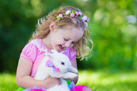 osterei: Kinder spielen mit echtem Kaninchen. Lachendes Kind auf Ostereiersuche mit weißen Haustierhäschen. Kleines Kleinkindmädchen spielt mit Tier im Garten. Sommer im Freien Spaß für Kinder mit Haustieren.