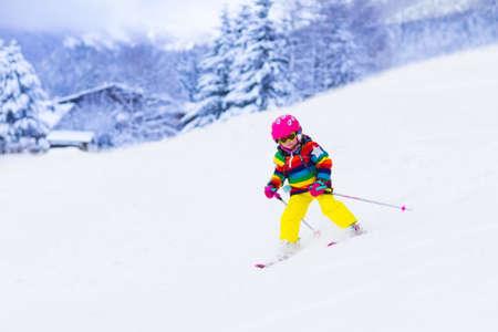 Esquí del niño en las montañas. Niño niño activo con casco de seguridad, gafas y polos. Carrera de esquí para los niños pequeños. Deporte de invierno para la familia. Niños esquí alpino lección en la escuela. Carreras de esquiador poco en la nieve
