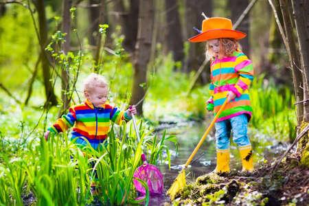 coger: Niños que juegan al aire libre. Niños en edad preescolar que cogen la rana con la red. El muchacho y la muchacha de la pesca en el río del bosque. Aventura kindergarten viaje de un día en la naturaleza salvaje, joven senderismo explorador y animales que miran.