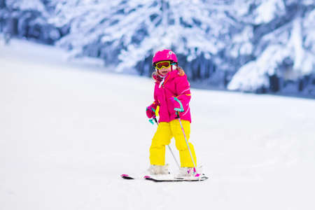 Child skiing in mountains. Active toddler kid with safety helmet, goggles and poles. Ski race for young children. Winter sport for family. Kids ski lesson in alpine school. Little skier racing in snow Stock Photo