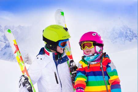 산에서 소년과 소녀 스키. 헬멧, 고글, 극 유아 아이 및 십대. 어린이를위한 스키 경주. 가족을위한 겨울 스포츠입니다. 아이들은 고산 학교에서 수업을