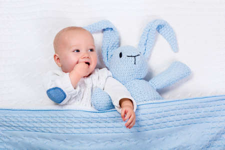 Funny little baby wearing a warm knitted jacket playing with toy bunny relaxing on white cable knit blanket in sunny nursery. Kids winter clothing and bedding. Hand made toys and textile for children. Stock Photo