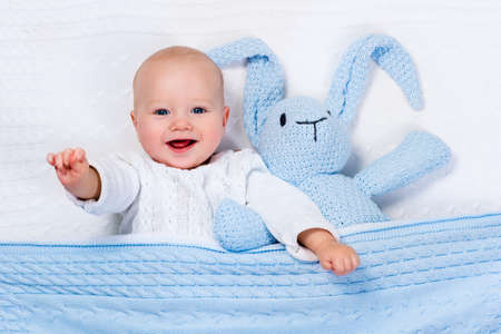 Funny little baby wearing a warm knitted jacket playing with toy bunny relaxing on white cable knit blanket in sunny nursery. Kids winter clothing and bedding. Hand made toys and textile for children. Stockfoto