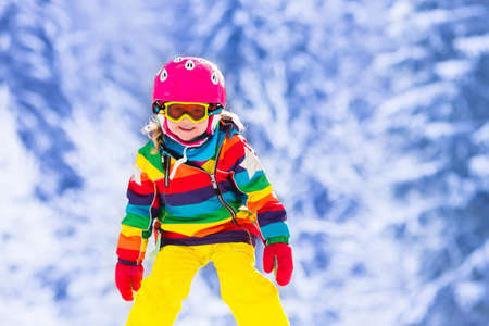 a young family: Child skiing in mountains. Active toddler kid with safety helmet, goggles and poles. Ski race for young children. Winter sport for family. Kids ski lesson in alpine school. Little skier racing in snow Stock Photo