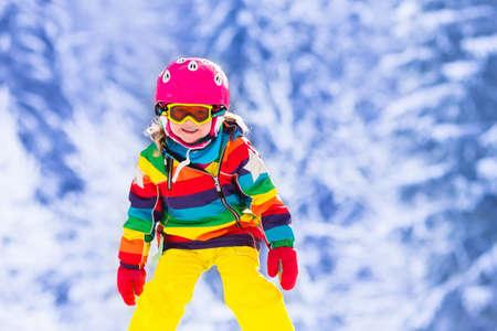 jovencitas: Esquí del niño en las montañas. Niño niño activo con casco de seguridad, gafas y polos. Carrera de esquí para los niños pequeños. Deporte de invierno para la familia. Niños esquí alpino lección en la escuela. Carreras de esquiador poco en la nieve