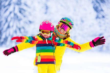 Moeder en weinig kind skiën in de Alpen bergen. Actieve moeder en peuter jongen met veiligheidshelm, veiligheidsbril en palen. Skiles voor jonge kinderen. Wintersport voor familie. Weinig skiër racen in de sneeuw Stockfoto