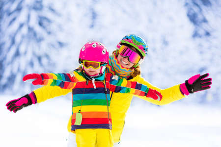 Mother and little child skiing in Alps mountains. Active mom and toddler kid with safety helmet, goggles and poles. Ski lesson for young children. Winter sport for family. Little skier racing in snow