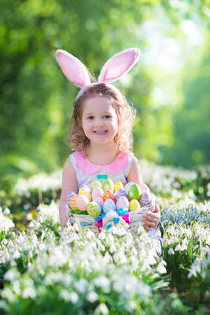 pequeño: Niña que se divierte en la búsqueda de huevos de Pascua. Los niños en orejas de conejo y traje de conejo. Los niños en busca de los huevos en el jardín. Hijo del niño que juega al aire libre. Niño riendo y sonriendo en un día de primavera