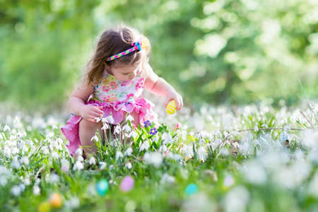 egg hunt: Little girl having fun on Easter egg hunt. Kids in blooming spring garden with crocus and snowdrop flowers. Children searching for eggs in the garden. Child putting colorful pastel eggs in a basket. Stock Photo