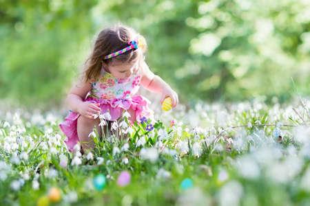 Niña que se divierte en la búsqueda de huevos de Pascua. Niños en jardín floreciente primavera con azafrán y flores campanilla. Los niños en busca de los huevos en el jardín. Niño que pone los huevos de colores pastel en una cesta. Foto de archivo