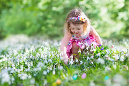 Little girl having fun on Easter egg hunt. Kids in blooming spring garden with crocus and snowdrop flowers. Children searching for eggs in the garden. Child putting colorful pastel eggs in a basket. Banque d'images