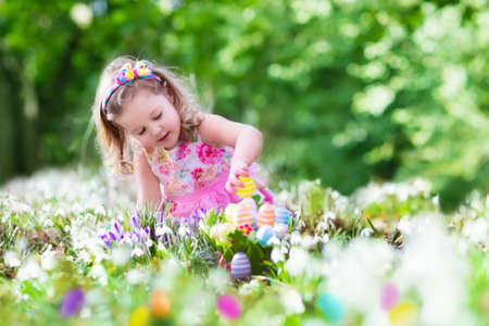eggs: Little girl having fun on Easter egg hunt. Kids in blooming spring garden with crocus and snowdrop flowers. Children searching for eggs in the garden. Child putting colorful pastel eggs in a basket. Stock Photo