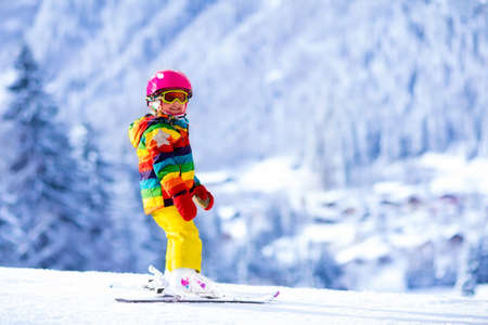 toddler: Child skiing in mountains. Active toddler kid with safety helmet, goggles and poles. Ski race for young children. Winter sport for family. Kids ski lesson in alpine school. Little skier racing in snow Stock Photo