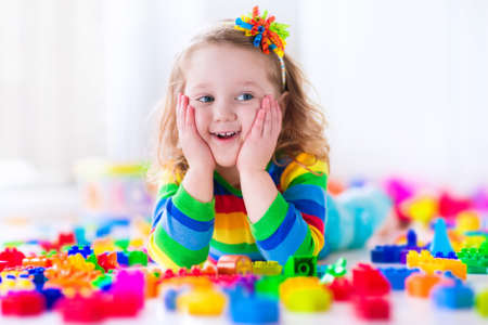 girl studying: Cute funny preschooler little girl in a colorful shirt playing with construction toy blocks building a tower in a sunny kindergarten room
