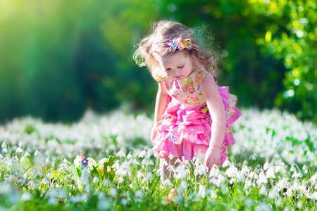 moño rosa: Muchacha del niño con los huevos de Pascua durante la búsqueda de huevos en el jardín con las primeras flores blancas