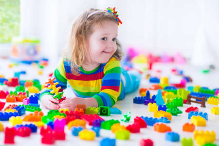 bedroom interior: Preschooler child playing with colorful toy blocks. Kids play with educational toys at kindergarten or day care. Preschool children build tower with plastic block. Toddler kid in nursery.