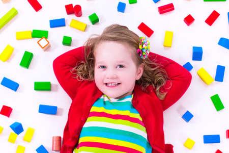 habitacion desordenada: Ni�o que juega con los juguetes de madera de colores. Ni�a con bloques de juguete educativos. Los ni�os juegan en la guarder�a o al preescolar. L�o en el cuarto de los ni�os. Ver desde arriba.