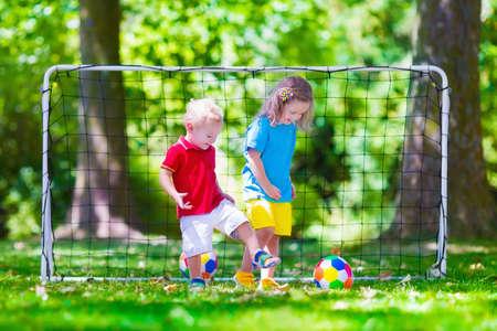 metas: Dos niños felices jugando fútbol europeo al aire libre en el patio de la escuela. Los niños juegan al fútbol. Deporte activo para el niño preescolar. Juego de bola para el joven equipo chico. Niño y niña marcar un gol en el partido de fútbol. Foto de archivo