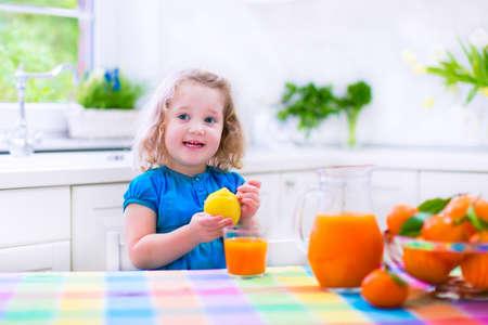 tomando jugo: Poco potable linda chica divertida zumo recién exprimido de naranja para el desayuno saludable en una cocina blanca con ventana en una soleada mañana de verano Foto de archivo