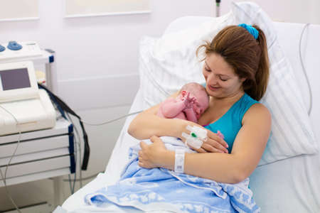 the newborn: Mother giving birth to a baby. Newborn baby in delivery room. Mom holding her new born child after labor. Female pregnant patient in a modern hospital. Parent and infant first moments of bonding.