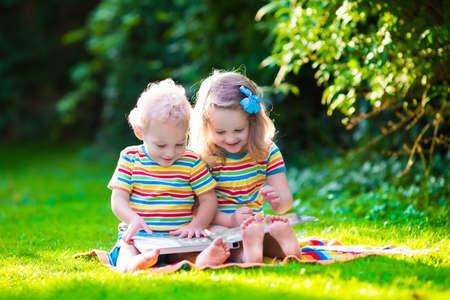 personas leyendo: Niños que leen un libro en el jardín de verano. Estudio de niños. Juego del muchacho y de la muchacha en el patio de la escuela. Amigos en edad preescolar juegan y aprenden. Hermanos hacer la tarea. Niño de Kindergarten y niños pequeños leen libros.