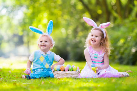 Little boy and girl having fun on Easter egg hunt. Kids in bunny ears and rabbit costume. Children with colorful eggs in a basket. Toddler kid and baby play outdoor on sunny spring day. Family holiday Foto de archivo