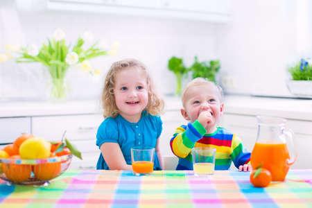tomando jugo: Linda niña divertida y de consumo del muchacho adorable bebé recién exprimido zumo de naranja para el desayuno saludable en una cocina blanca con ventana en una soleada mañana de verano Foto de archivo