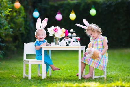 Weinig jongen en meisje spelen speelgoed theekransje buiten. Kinderen met bunny oren op Easter egg hunt. Kinderen spelen in de tuin in het voorjaar. Peuter en baby met speelgoed konijn en pop gerechten. familiefeest Stockfoto