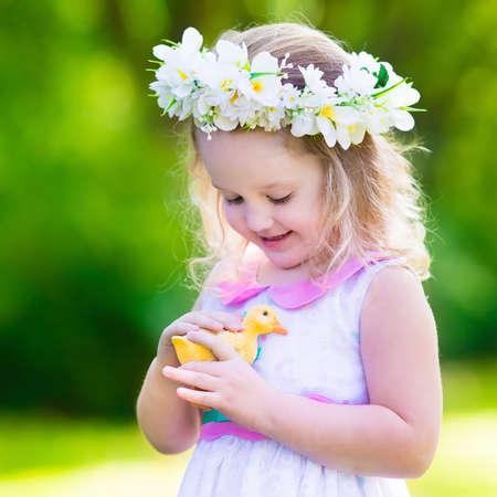 Petite fille amusant sur la chasse aux ?ufs de Pâques. Kid couronne de fleurs en jouant avec le canard de jouet ou de poulet. Les enfants à la recherche d'oeufs dans le jardin. Toddler Outdoor Enfants. enfant heureux rire et sourire.