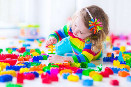 Preschooler child playing with colorful toy blocks. Kids play with educational toys at kindergarten or day care. Preschool children build tower with plastic block. Toddler kid in nursery.