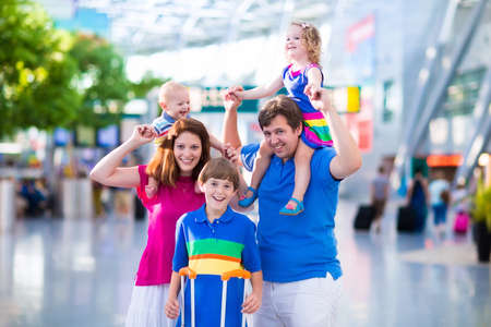 family vacation: Family traveling with kids. Parents with children at international airport with luggage. Mother and father hold baby, toddler girl and boy flying by airplane. Travel with child for summer vacation.