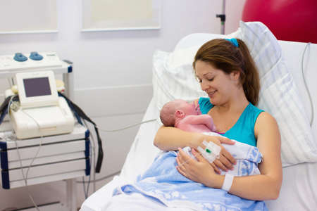 Mother giving birth to a baby. Newborn baby in delivery room. Mom holding her new born child after labor. Female pregnant patient in a modern hospital. Parent and infant first moments of bonding.