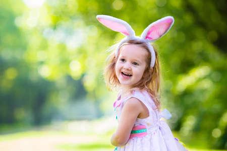 Petite fille amusant sur la chasse aux ?ufs de Pâques. Enfants dans les oreilles de lapin et le costume de lapin. Les enfants avec des oeufs colorés dans un panier. kid enfant jouant en plein air. Enfant tenant un tableau blanc blanc pour votre texte.