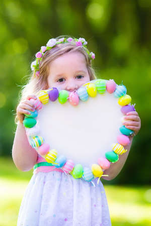 sun  flower: Little girl having fun on Easter egg hunt. Kids in bunny ears and rabbit costume. Children with colorful eggs in a basket. Toddler kid playing outdoor. Child holding blank white board for your text.