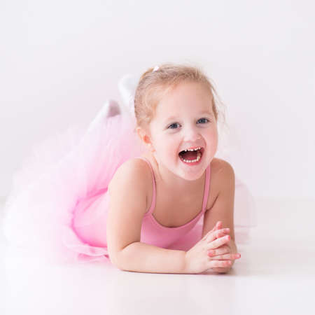 kids class: Little ballerina girl in a pink tutu. Adorable child dancing classical ballet in a white studio. Children dance. Kids performing. Young gifted dancer in a class. Preschool kid taking art lessons.