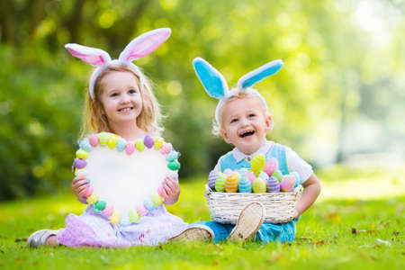 bebes niñas: Niño pequeño y muchacha que se divierte en búsqueda de huevos de Pascua. Los niños en orejas de conejo y traje de conejo. Los niños con coloridos huevos en una cesta. Niño niño y el bebé juegan al aire libre. Tarjeta en blanco para el texto.