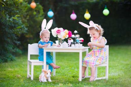 gemelos niÑo y niÑa: niño y niña juegan partido de té del juguete al aire libre. Los niños con orejas de conejo en búsqueda de huevos de Pascua. Niños jugando en el jardín en primavera. Niño y el bebé con platos de conejo de juguete y muñeca. celebración familiar