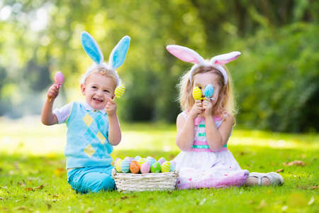 Little boy and girl having fun on Easter egg hunt. Kids in bunny ears and rabbit costume. Children with colorful eggs in a basket. Toddler kid and baby play outdoor on sunny spring day. Family holiday Stock Photo