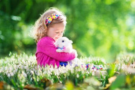 pascuas navide�as: Muchacha linda del ni�o que juega con el conejo real en jard�n floreciente primavera. Ni�o en la b�squeda de huevos de Pascua. Ni�o con los huevos de colores y mascota conejo. Los ni�os juegan con los animales dom�sticos. Los ni�os la alimentaci�n animal. Familia con los animales.
